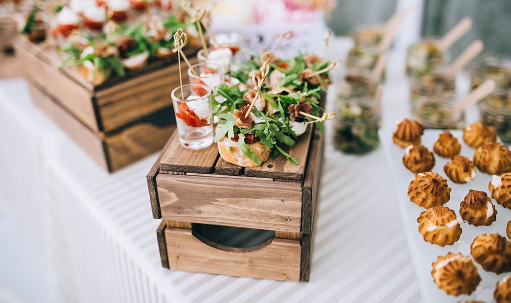 food arranged on a white cloth covered table with small crates used for height.