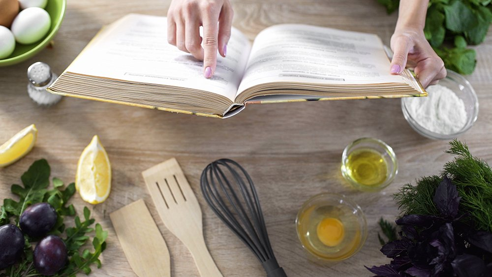 Counter top scattered with food and woman's hands holding open a cook book
