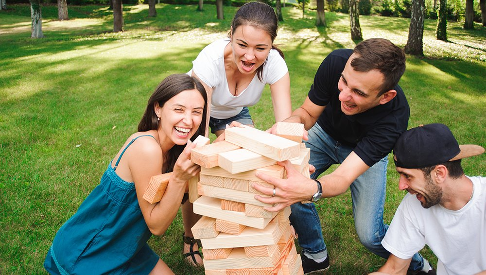 4 people playing giant jenga game in the grass.
