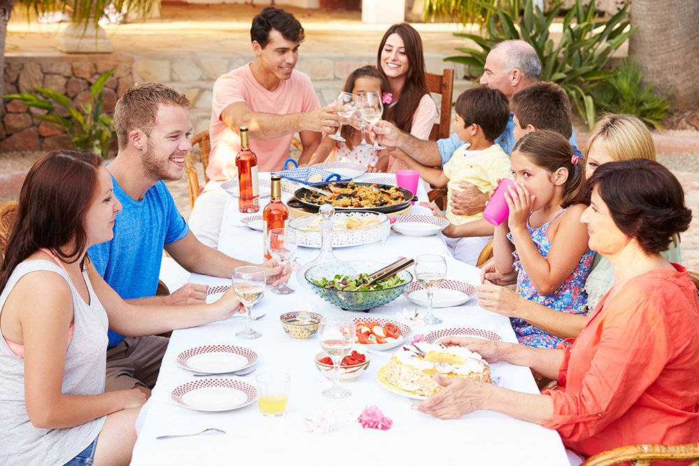 Family gathered around outdoor table sharing a meal