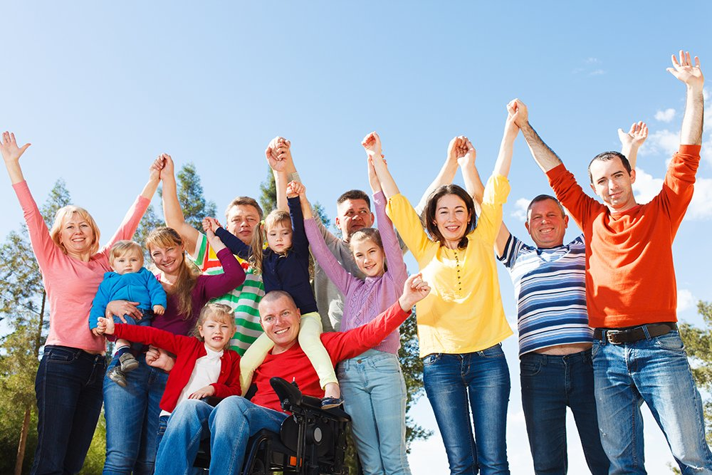 Large family outside on sunny day with hands raised in the air.