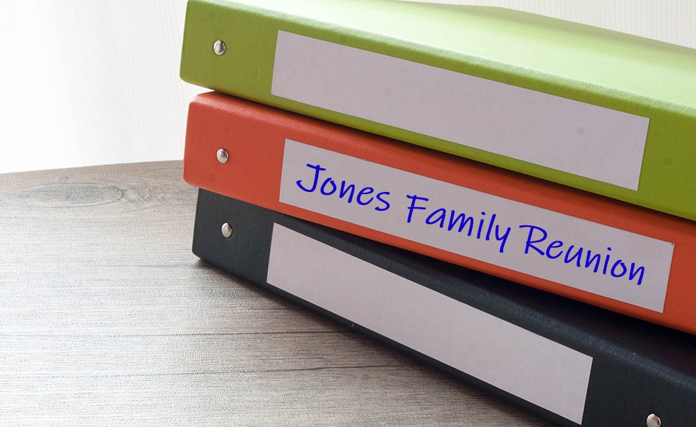 3 binders, black, orange and green sitting on table top. The orange binder is labeled Jones Family Reunion.