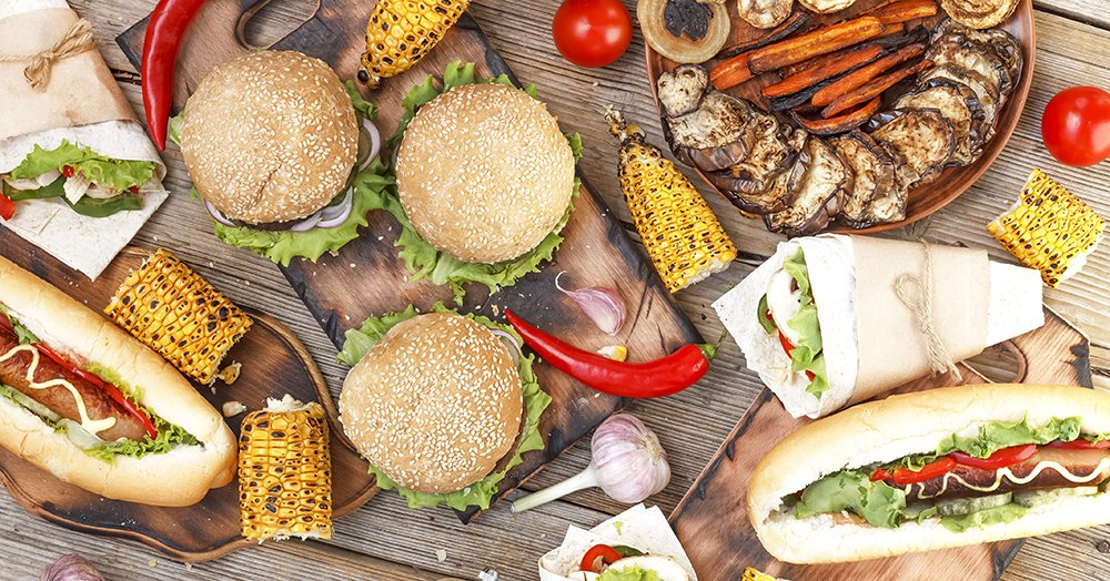 burgers, hotdogs and grilled foods on a picnic table top