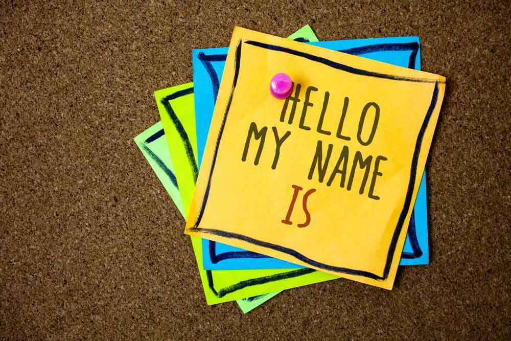"Cork board with post its hung with thumb tack that reads ""Hello My Name Is"""