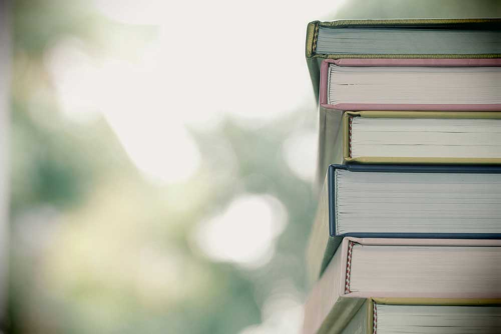 Stack of books with blurred trees in background