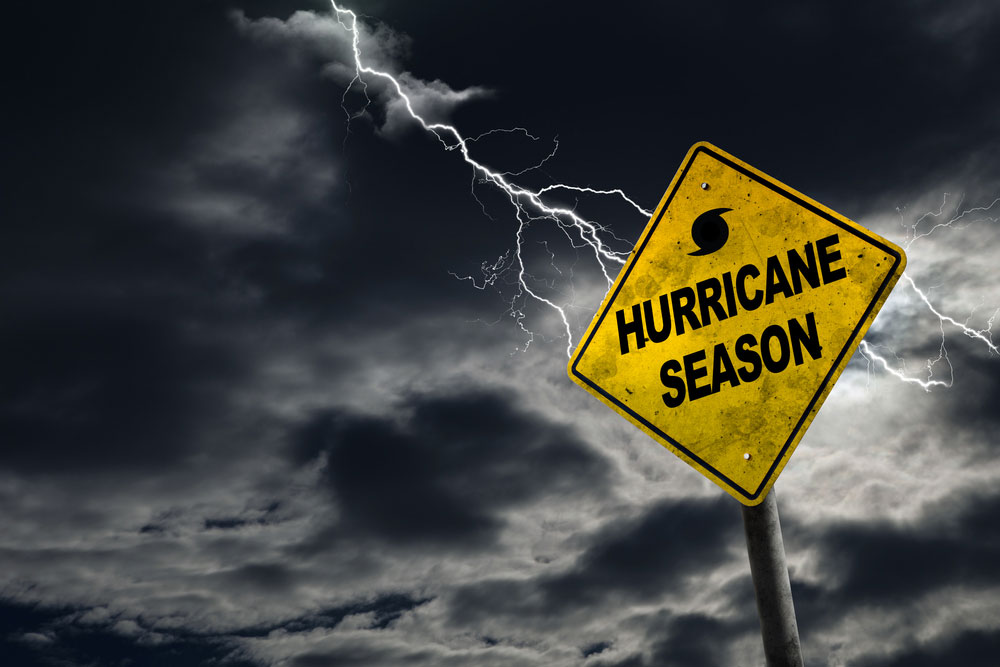 Hurricane Season yellow caution sign in front of stormy background with lighning