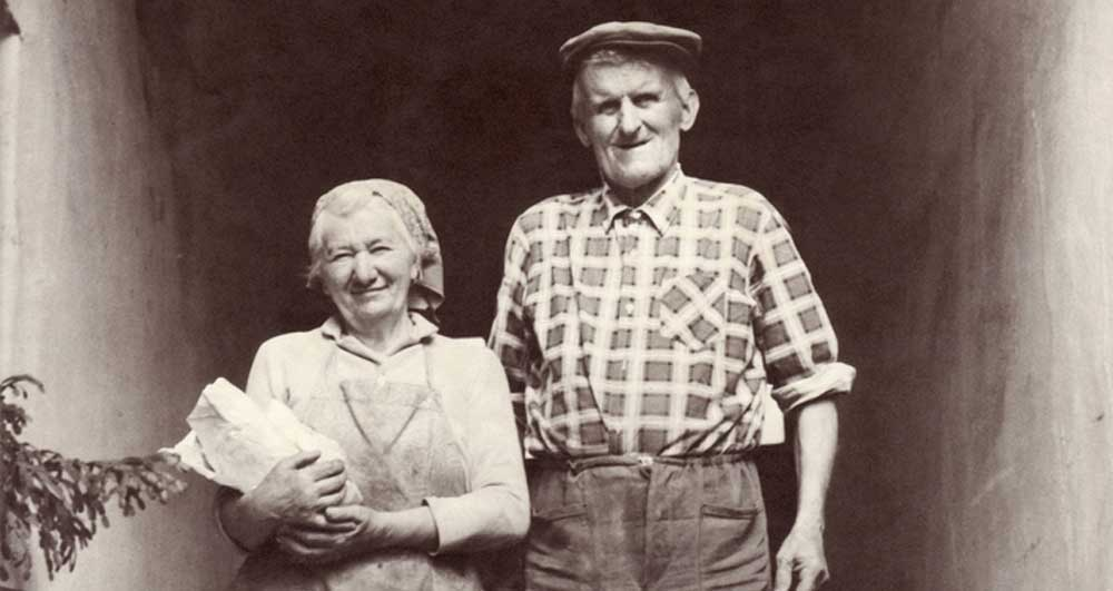 old photo of an older couple in farm clothes.