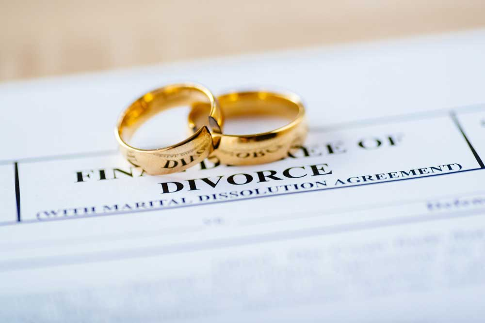 two wedding rings sitting on top of divorce papers