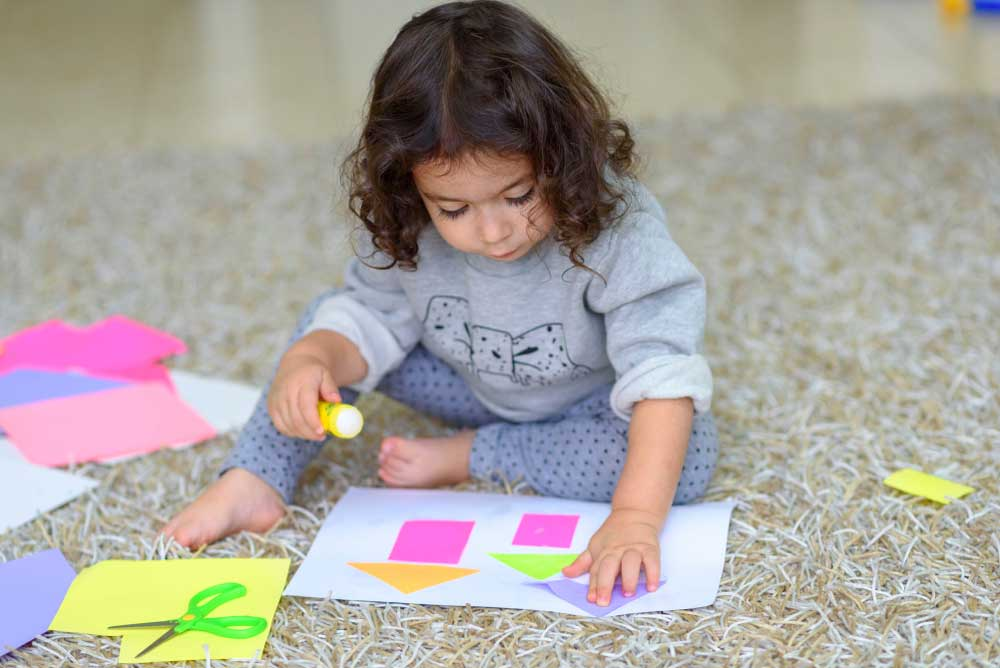 Toddler gluing shapes onto a paper