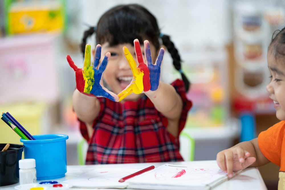 Small girl with hands painted blue yellow and red