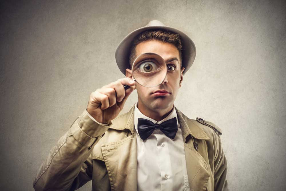 man dressed as a detective looking through magnifying glass on grey background