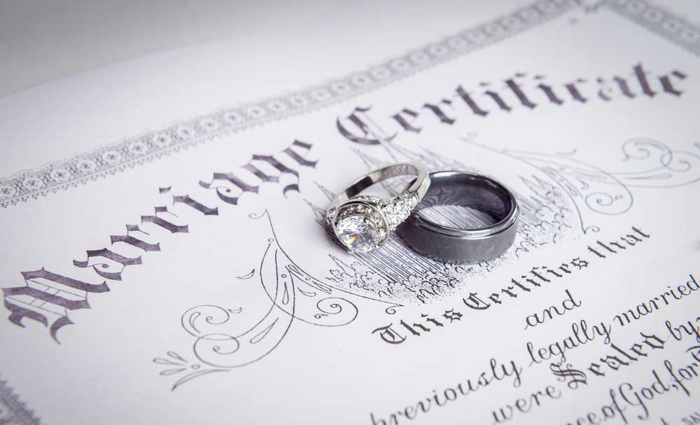 A marriage certificate with wedding rings resting on top