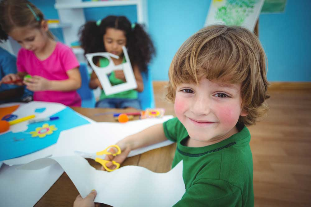 Pre school child sitting at table doing crafts