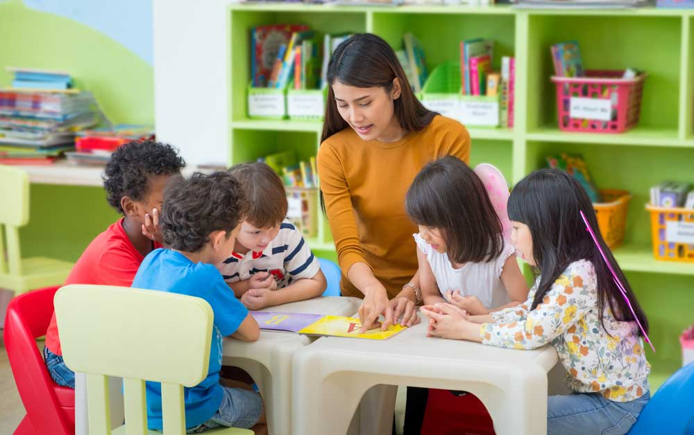 Teacher surrounded by small children at a table