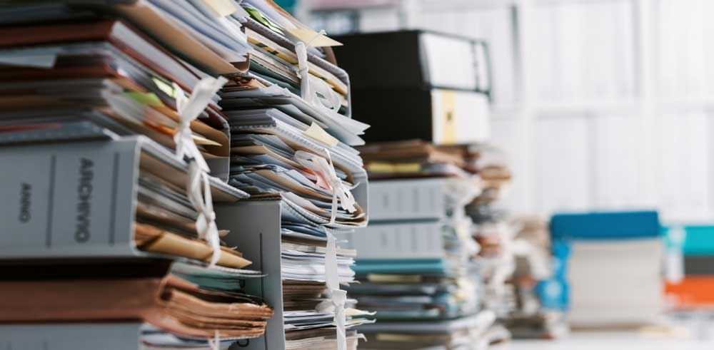 Stacks of binders and files on a table