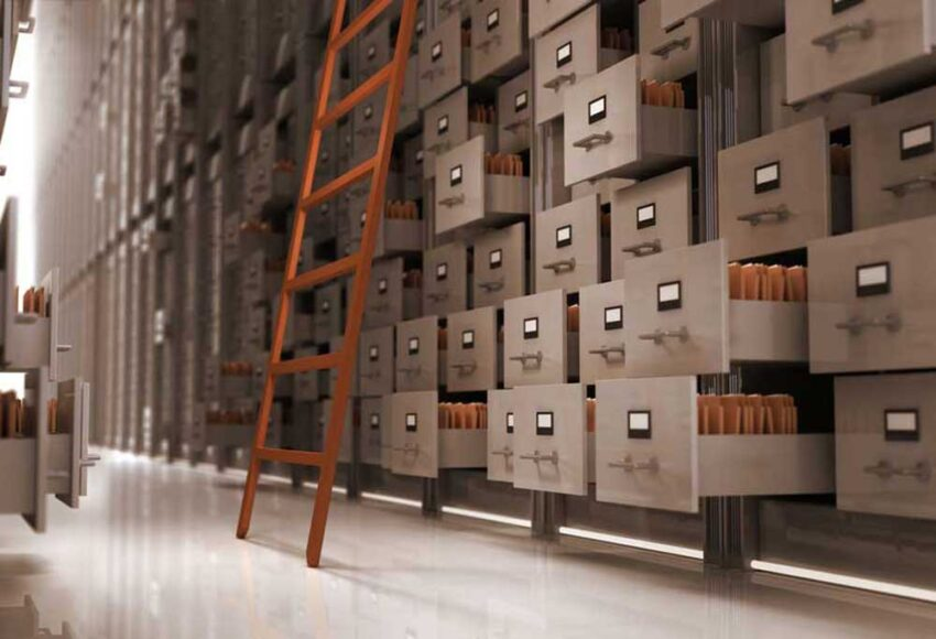 Large wall of file cabinets with drawers open with a wooden ladder leaning against them.