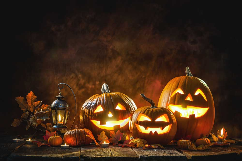 Jack o lanterns on wooden table on dark background