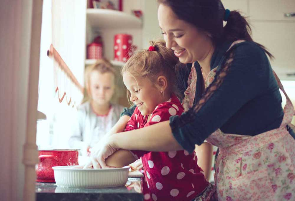 Mother and daughters baking together