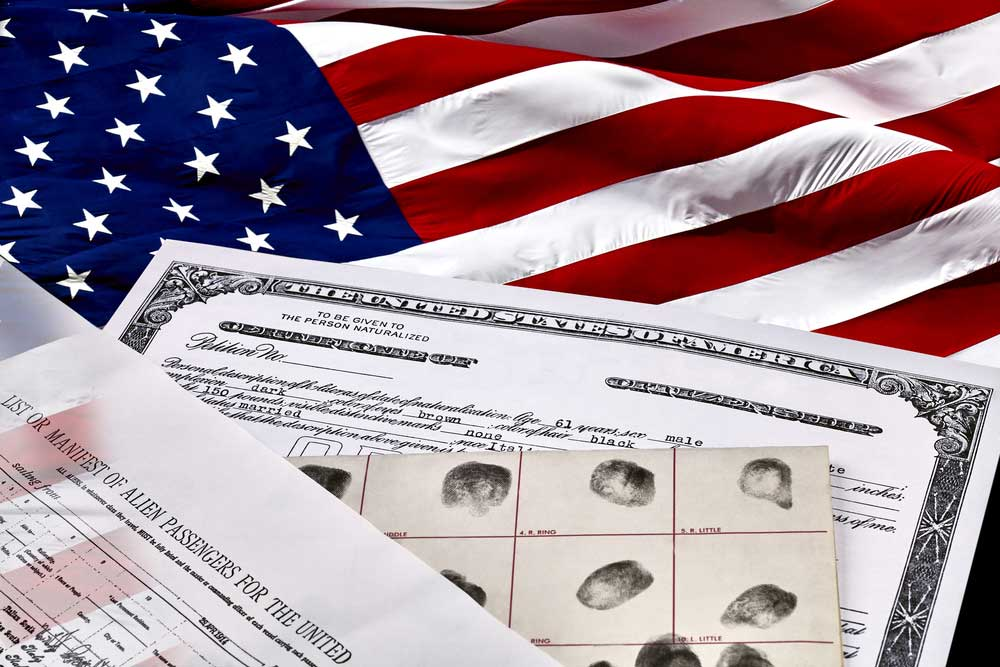 A birth certificate, finger print card, and passenger manifest laying on an American flag