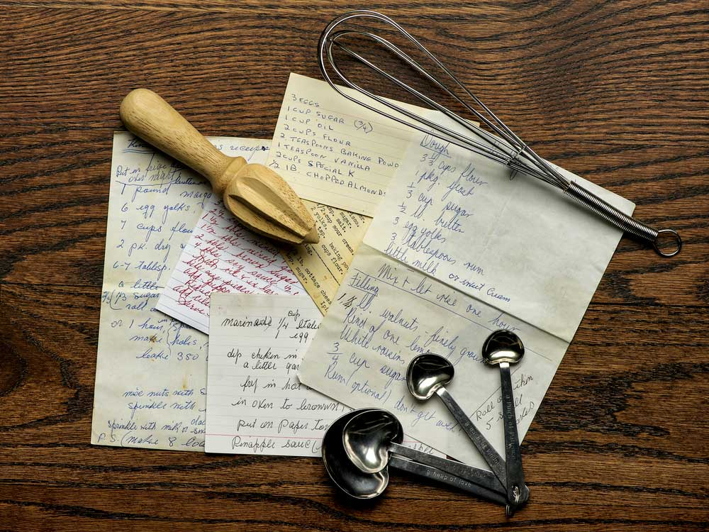 hand written recipes and cooking utensils on a wooden table