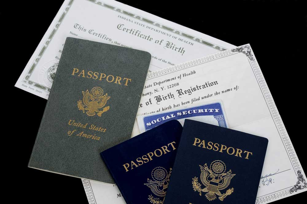 Birth certificates, social security cards and passports on a black background.
