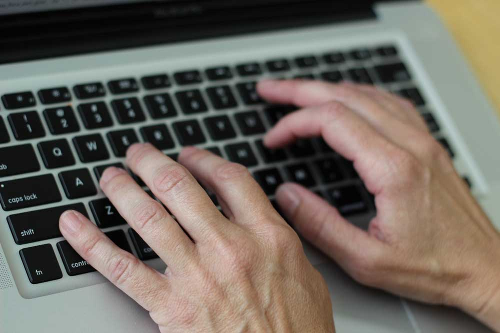 close up of a set of hands typing on a laptop keyboard.