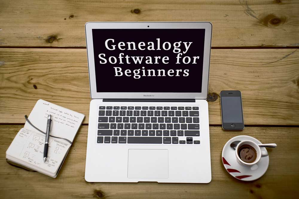 """computer on desk with notebook , coffee, and cell phone. Computer screen reads """"Genealogy Software for Beginners"""""""
