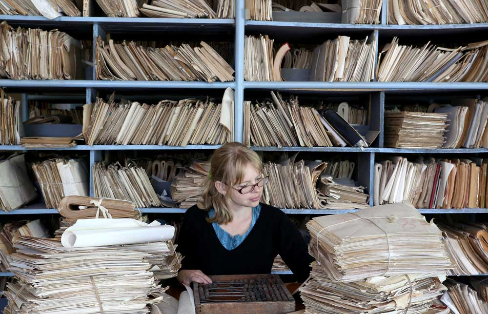 Woman sitting at table among huge stacks of papers with full shelves in the background.