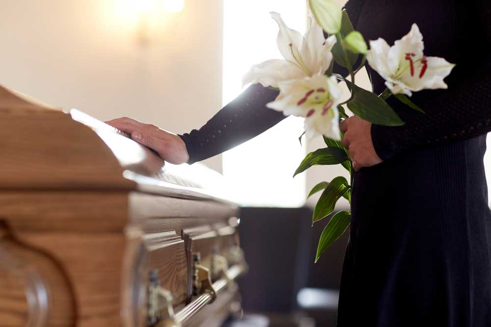 cropped view of a mourner holding flowers with their hand on a casket.