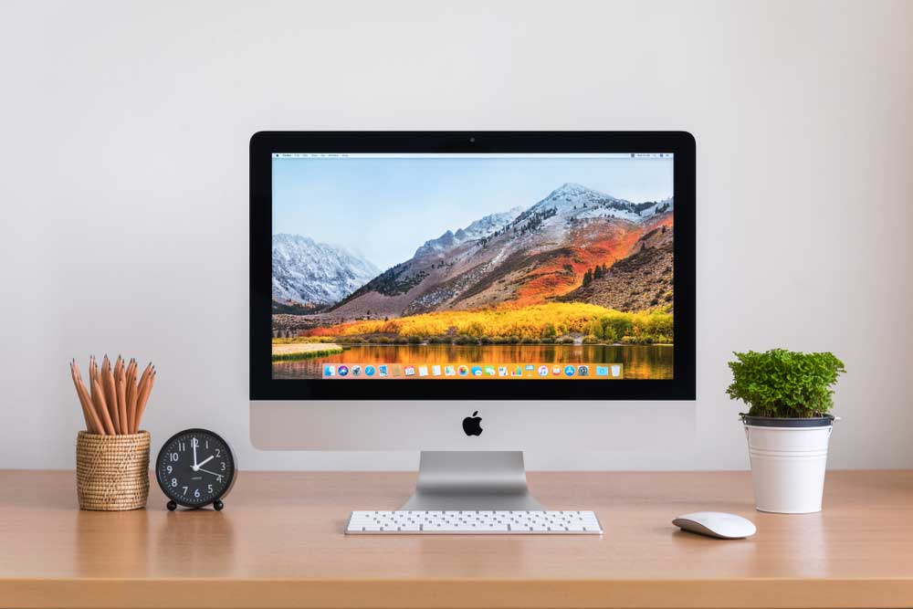 Apple brand computer on a desk with pencil holder, clock, and small plant.
