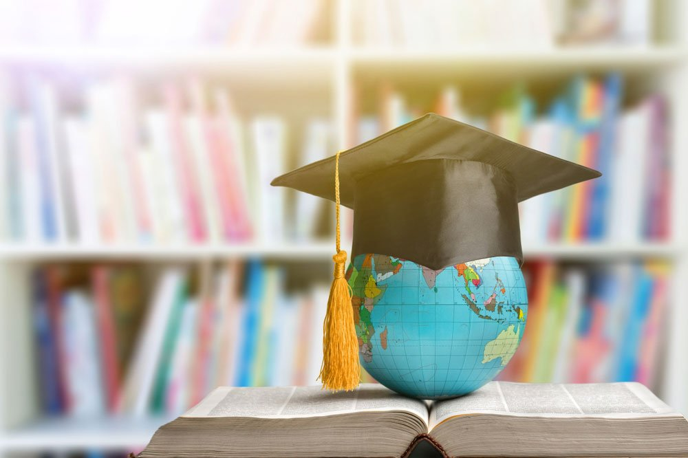 Globe wearing graduation cap resting on open book in front of bookshelf