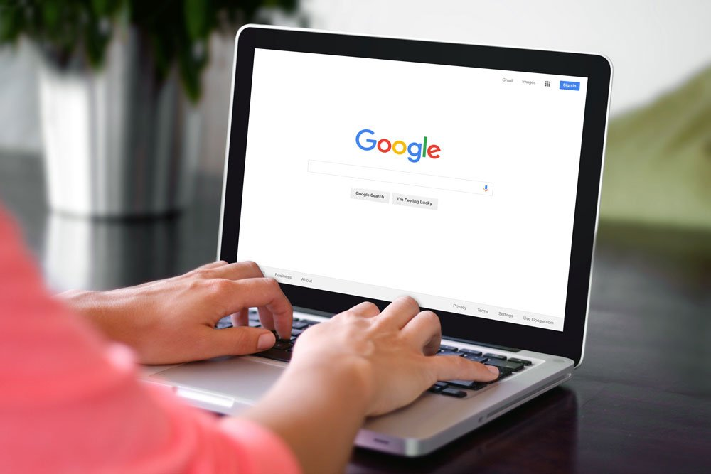hands typing on laptop with google search open on screen