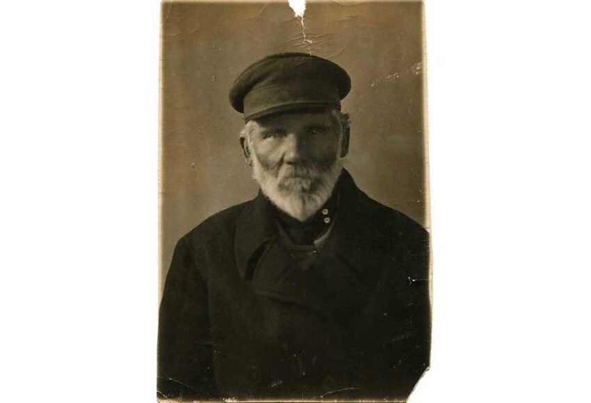 sepia toned photo of man with grey beard in hat and coat with cracks and scratches