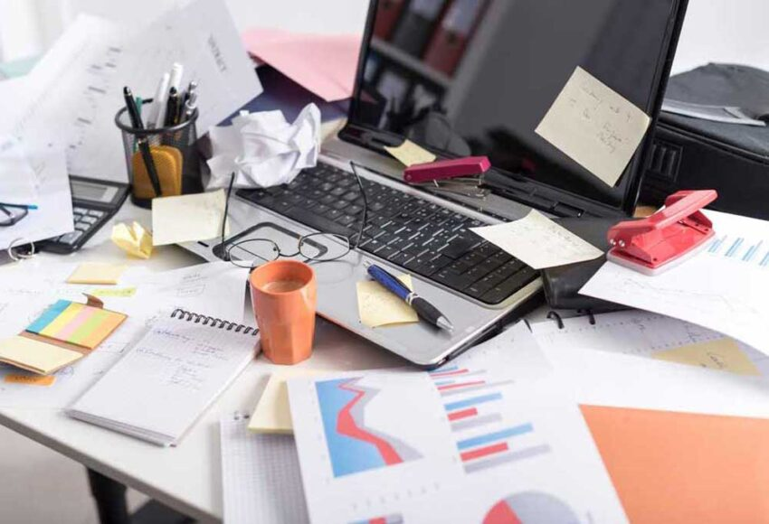 cluttered office desk that needs to be cleaned