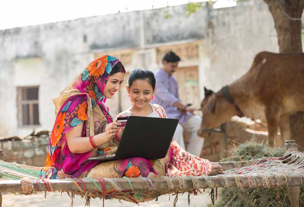 Indian family outdoors looking at a laptop