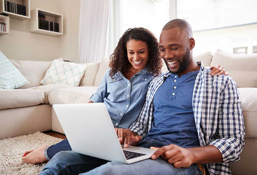 Man and woman sitting on living room floor looking at laptop screen