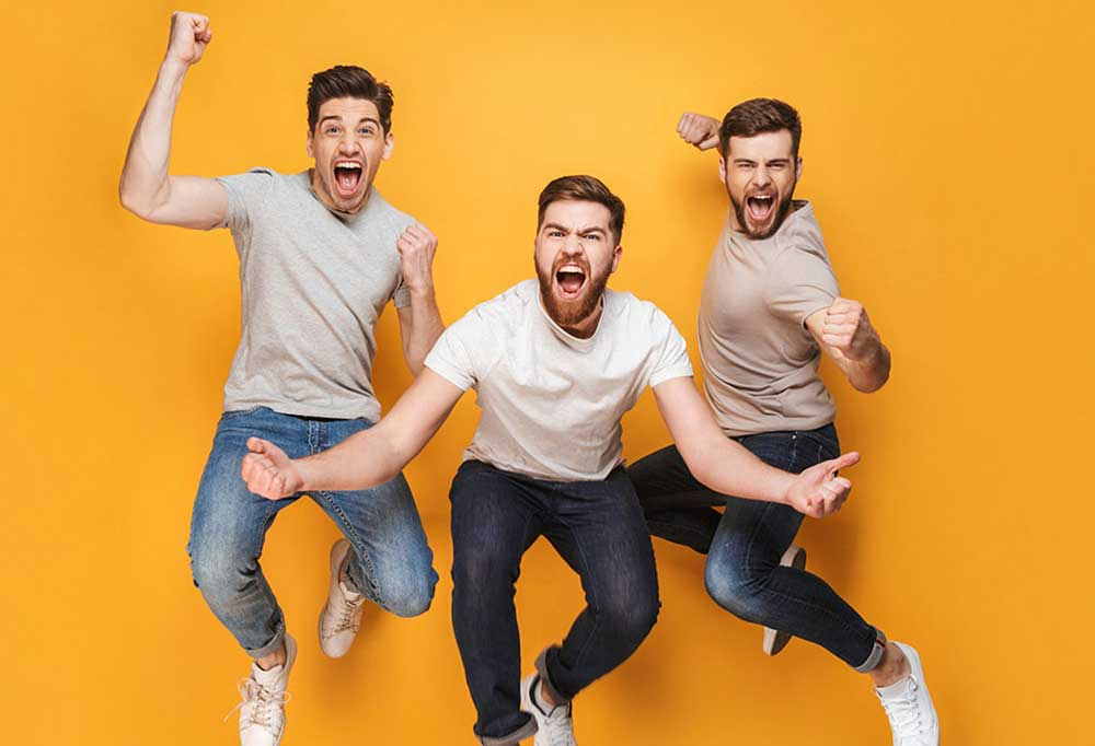 3 men jumping into the air in front of a yellow background